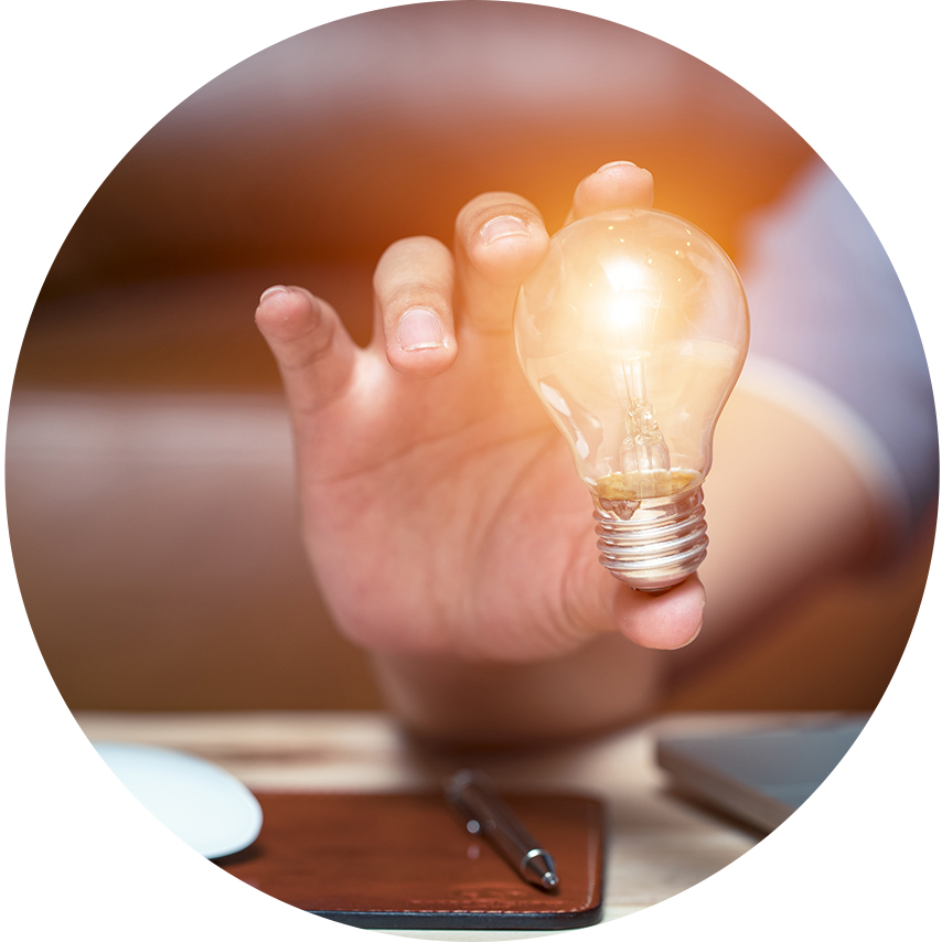 Hand holding a lit up lightbulb near a laptop.