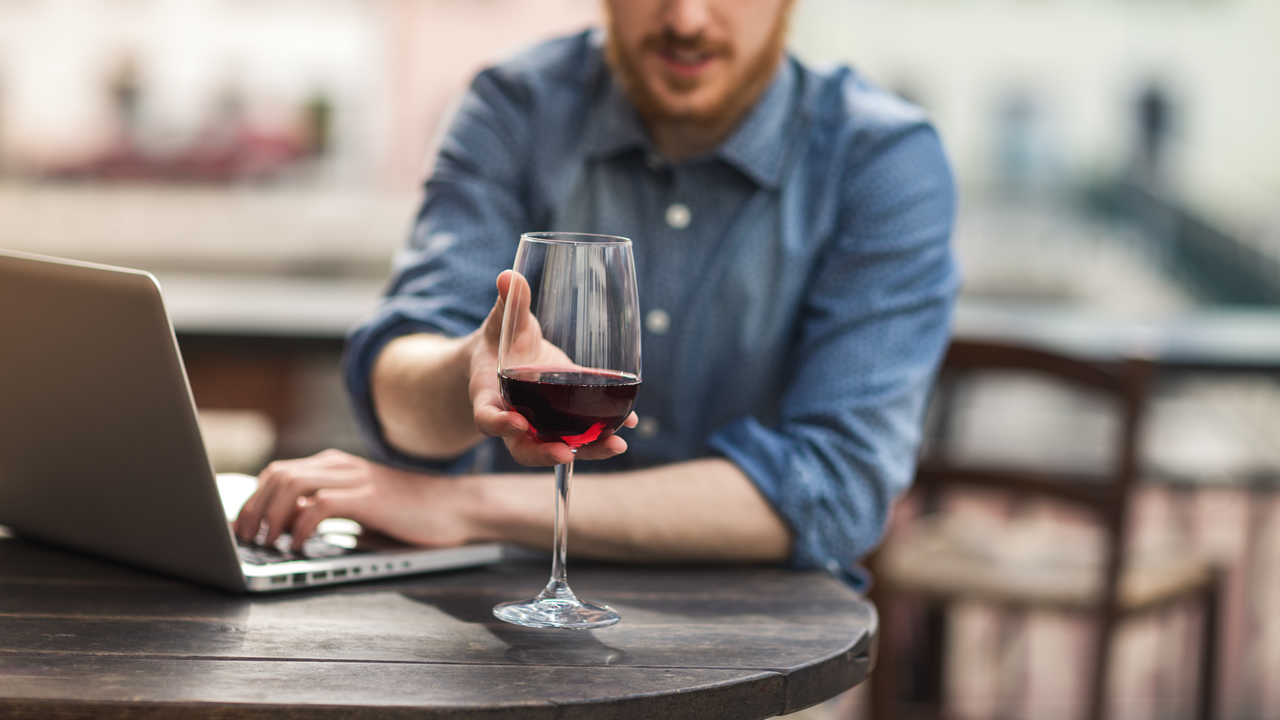 Person working on a laptop, reaching for a glass of red wine.
